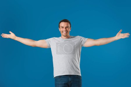 cheerful man standing with open arms and smiling at camera isolated on blue