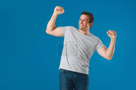 Photo for Excited man triumphing and looking away isolated on blue - Royalty Free Image
