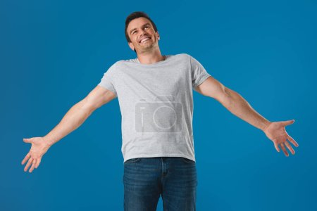 happy man standing with open arms and looking up isolated on blue