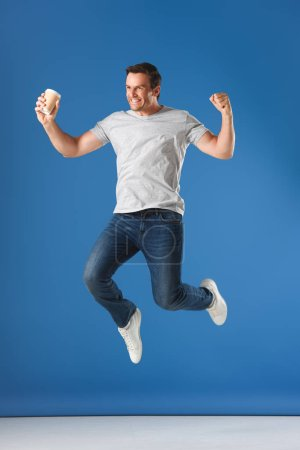 Photo for Excited man with coffee to go jumping and triumphing on blue - Royalty Free Image