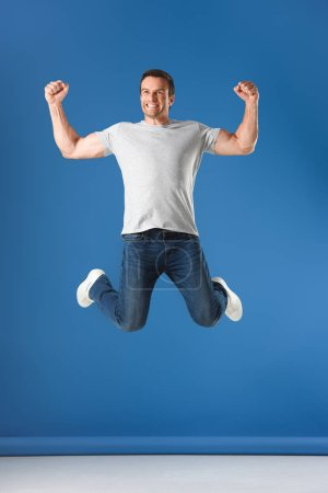 Photo for Excited man jumping and triumphing on blue - Royalty Free Image