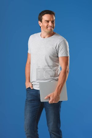happy handsome man holding laptop and looking away isolated on blue