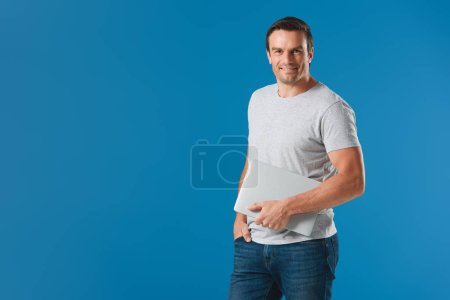 happy handsome man holding laptop and smiling at camera isolated on blue