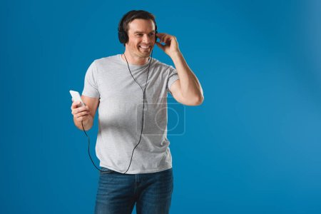 happy man in headphones listening music with smartphone and looking away isolated on blue