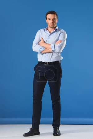 full length view of handsome man standing with crossed arms and looking at camera on blue