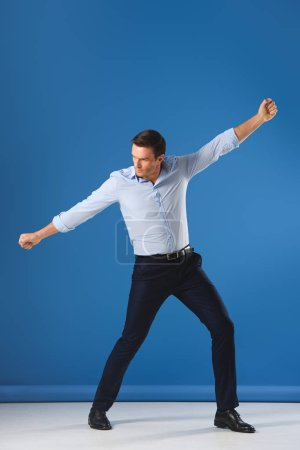 Photo for Full length view of handsome man posing and looking away on blue - Royalty Free Image