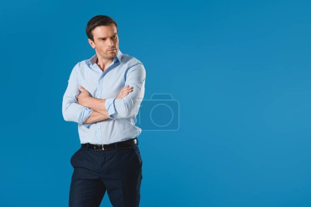 serious man standing with crossed arms and looking away isolated on blue