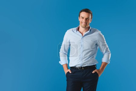 Photo for Handsome man standing with hands in pockets and smiling at camera isolated on blue - Royalty Free Image