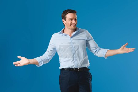 happy handsome man standing with open arms and looking away isolated on blue