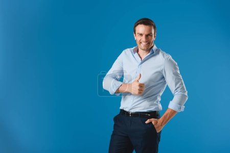 handsome businessman showing thumb up and smiling at camera isolated on blue