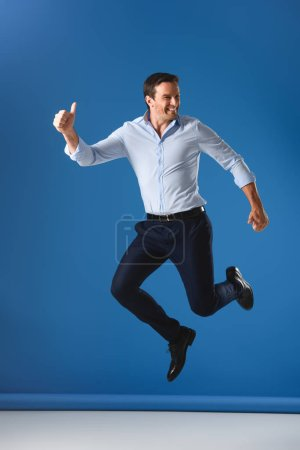cheerful handsome man showing thumbs up and jumping on blue