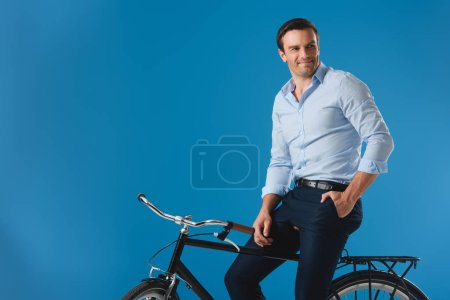 handsome smiling man sitting on bike and looking away isolated on blue