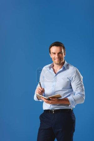 Photo pour Bel homme d'affaires écrivant dans un carnet et souriant à la caméra isolé sur bleu - image libre de droit