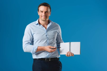 handsome businessman pointing at blank notebook and smiling at camera isolated on blue