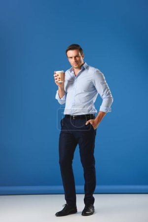 handsome man holding disposable coffee cup and looking at camera on blue