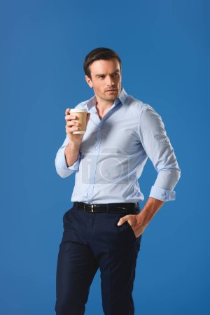 handsome man holding disposable coffee cup and looking away isolated on blue