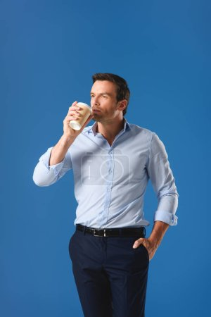handsome man drinking from paper cup and looking away isolated on blue