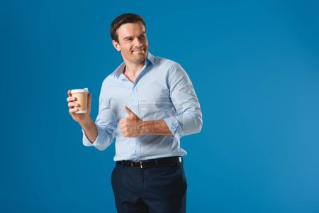 handsome smiling man holding coffee to go and showing thumb up isolated on blue