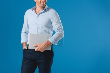 cropped shot of smiling man holding laptop isolated on blue