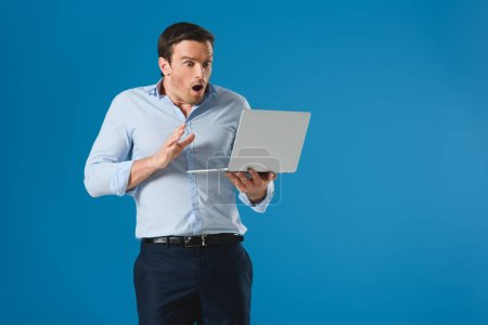 shocked man holding and using laptop isolated on blue