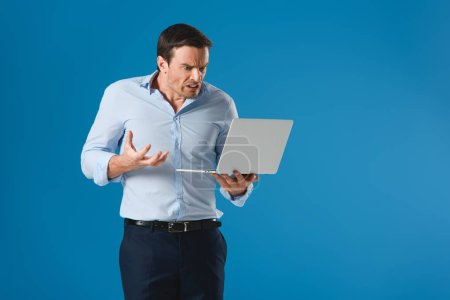 angry man holding and using laptop isolated on blue