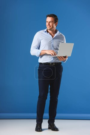 full length view of handsome smiling man holding laptop and looking away on blue