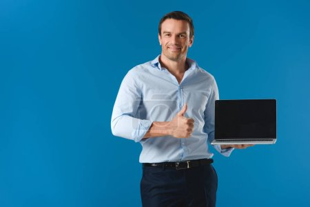 handsome man holding laptop with blank screen, showing thumb up and smiling at camera isolated on blue