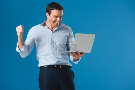 cheerful handsome man holding laptop isolated on blue
