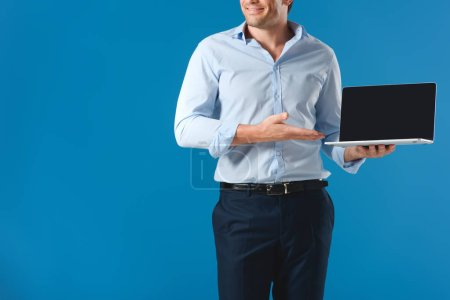 cropped shot of smiling man holding laptop with blank screen isolated on blue