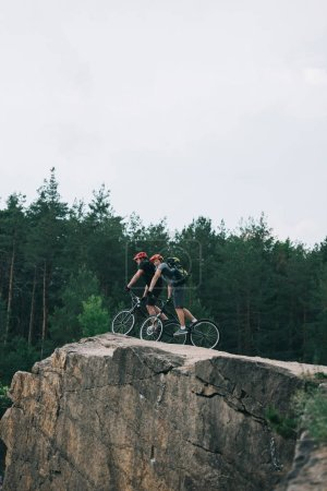 distant view of male extreme cyclists in protective helmets riding on mountain bicycles on rocky cliff in forest