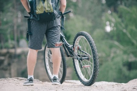 cropped image of male cyclist with backpack standing near bicycle