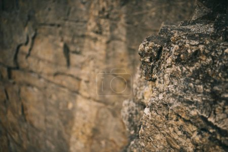 selective focus of surface of rocky cliff on blurred background