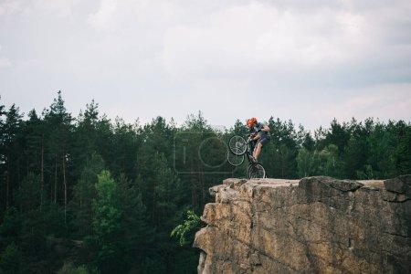 Foto de Vista de ciclistas extremos macho en cascos protectores haciendo acrobacias sobre bicicletas de montaña en el acantilado rocoso en bosque - Imagen libre de derechos