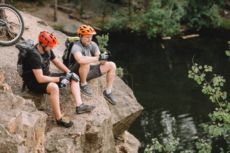 high angle view of friends cyclists with backpacks resting with sport bottle of water on rocky cliff near river in forest