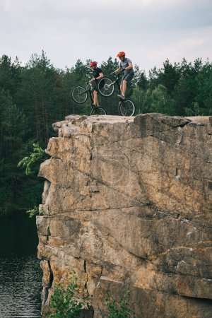 deux cyclistes extrêmes masculins en casque de protection sautant sur des vélos de montagne sur une falaise rocheuse en forêt