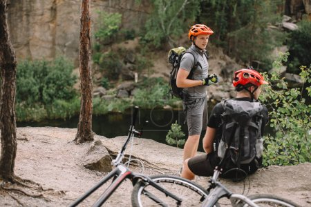two male friends with backpacks and bicycles resting near river in forest