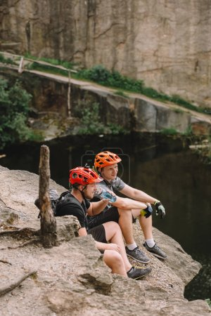 Sportsmen in protective helmets resting with apple and sport bottle of water on rocky cliff