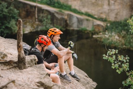 two male hikers in protective helmets with backpacks resting with water and apple on rocky cliff