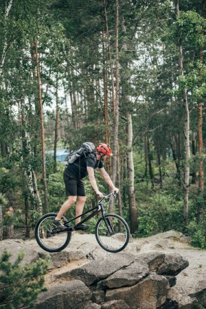 male extreme cyclist in protective helmet riding on mountain bicycle in forest