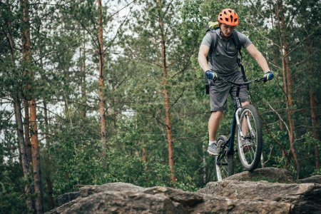 male cyclist in protective helmet performing stunt on mountain bike in forest
