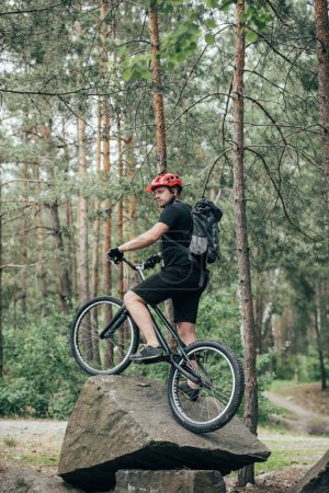 male extreme cyclist in protective helmet standing on mountain bicycle on stone in forest