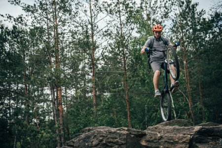 low angle view of male biker in protective helmet doing stunt on mountain bike in forest