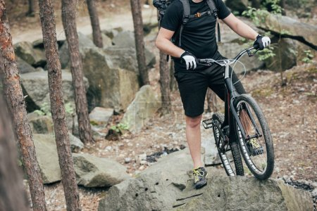 cropped image of male extreme cyclist in protective helmet standing with mountain bicycle on stone in forest