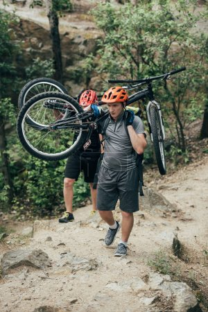 Photo for Two male extreme cyclists in helmets carrying mountain bikes in forest - Royalty Free Image