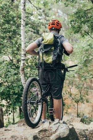 rear view of male cyclist in protective helmet with backpack standing with bicycle in forest