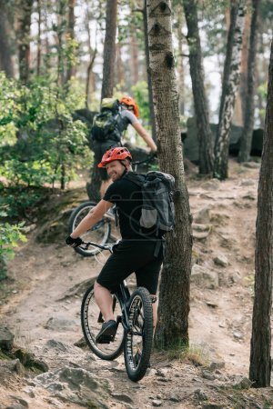 Photo for Smiling male extreme cyclist riding on mountain bicycle with friend in forest - Royalty Free Image