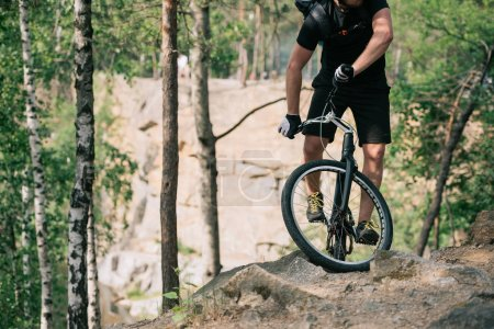 cropped image of male extreme cyclist with backpack doing stunt on bmx in forest