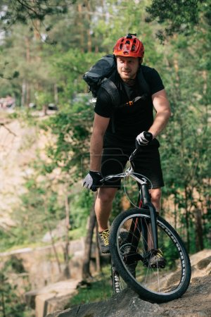smiling male trial biker in protective helmet riding on mountain bicycle in forest