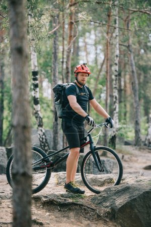 young male extreme cyclist in protective helmet standing with mountain bicycle in forest