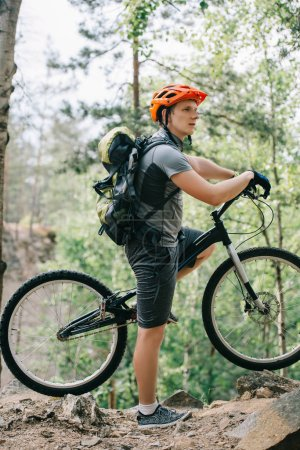 side view of male cyclist in helmet with backpack standing with mountain bike in forest